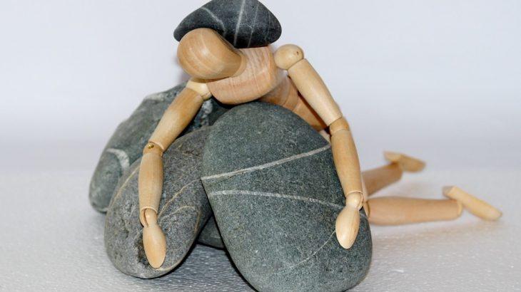 wooden man slumped over rocks